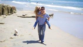 Attraktiva par med deras labradorvalp på stranden Arkivfoto