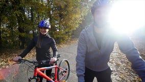 Attraktiva par som går med cyklar i hösten, parkerar Vektorillustration för din design långsam rörelse arkivfilmer