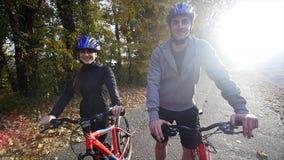 Attraktiva par som går med cyklar i hösten, parkerar Vektorillustration för din design långsam rörelse stock video