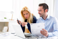 Attraktiva par som gör administrativ skrivbordsarbete fotografering för bildbyråer