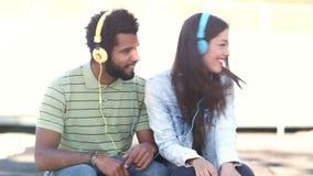 Attraktiva par som har gyckel som lyssnar till musik med hörlurar arkivfilmer