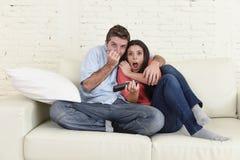 Attraktiva par som har rolig hemmastadd tyckande om hållande ögonen på show för televisionfasafilm Arkivfoton