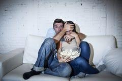 Attraktiva par som har rolig hemmastadd tyckande om hållande ögonen på show för televisionfasafilm Arkivbild