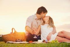 Attraktiva par som kysser på romantisk picknick Arkivfoton