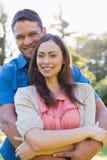 Attraktiva par som ler på kameran och krama Arkivfoto