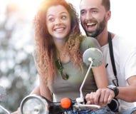 Attraktiva par som rider en sparkcykel på en solig dag i staden royaltyfri bild