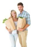 Attraktiva par som rymmer deras livsmedelsbutikpåsar Arkivfoto