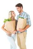 Attraktiva par som rymmer deras livsmedelsbutikpåsar Royaltyfria Bilder