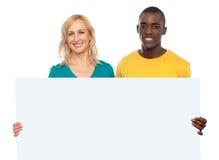 Attraktiva par som rymmer det vita blanka annonsbrädet Fotografering för Bildbyråer