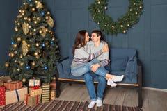 Attraktiva par som sitter på en soffa som omfamnar ömt med en julgran i bakgrunden arkivbilder