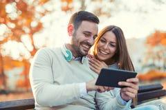 Attraktiva par som talar och ser den digitala minnestavlan Arkivbilder