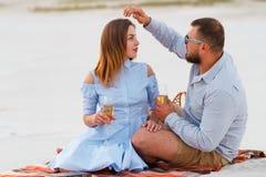 Attraktiva par som tillsammans sitter och att se sig, lyckliga par som tycker om picknicken på den vita sandstranden och dricker  Arkivfoton