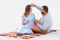 Attraktiva par som tillsammans sitter och att se sig, lyckliga par som tycker om picknicken på den vita sandstranden och dricker  Royaltyfri Foto