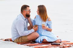 Attraktiva par som tillsammans sitter och att se sig, lyckliga par som tycker om picknicken på den vita sandstranden och dricker  Royaltyfria Foton