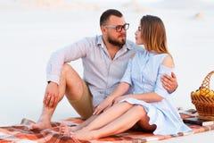 Attraktiva par som tillsammans sitter på den vita sandstranden som ser sig, lyckliga par som tycker om picknicken på stranden och Arkivbilder