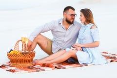 Attraktiva par som tillsammans sitter på den vita sandstranden som ser sig, lyckliga par som tycker om picknicken på stranden och Royaltyfria Foton