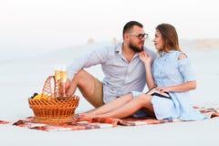 Attraktiva par som tillsammans sitter på den vita sandstranden som ser sig, lyckliga par som tycker om picknicken på stranden och Arkivfoton
