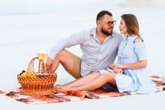 Attraktiva par som tillsammans sitter på den vita sandstranden som ser sig, lyckliga par som tycker om picknicken på stranden och Royaltyfria Bilder