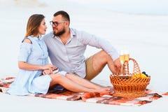 Attraktiva par som tillsammans sitter på den vita sandstranden som ser sig, lyckliga par som tycker om picknicken på stranden och Royaltyfri Bild