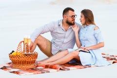 Attraktiva par som tillsammans sitter på den vita sandstranden som ser sig, lyckliga par som tycker om picknicken på stranden och fotografering för bildbyråer