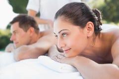 Attraktiva par som tycker om parmassagepoolsiden Royaltyfria Bilder