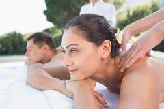 Attraktiva par som tycker om parmassagepoolsiden Arkivbilder