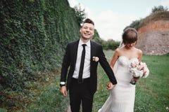 Attraktiva parnygifta personer g?r tillbaka p? en slinga brud och brudgum som kramar, i att blomma v?rtr?dg?rden royaltyfri foto
