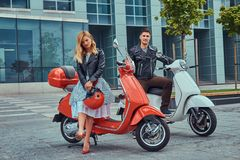 Attraktiva romantiska par, en stilig man och sexig kvinnlig som står med två retro italienska sparkcyklar mot a arkivfoton