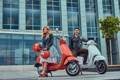 Attraktiva romantiska par, en stilig man och sexig kvinnlig som står med två retro italienska sparkcyklar mot a arkivbild