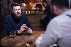 Attraktiva sk?ggiga m?n som dricker whisky i en bar fotografering för bildbyråer