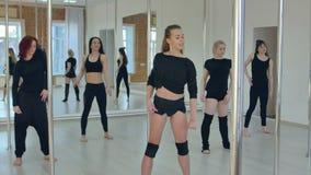Attraktiva sportflickor som sträcker för poldansgrupp i idrottshall med fönster stock video