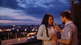 Attraktiva tillfälligt påkläddpar tycker om en romantisk promenad tillsammans med stadssikten Kvinnan gör en gest mannen för att  lager videofilmer