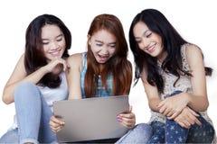 Attraktiva tonårs- flickor som använder bärbara datorn i studio Arkivbild