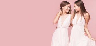 Attraktiva två härliga flickor på rosa bakgrund Royaltyfria Foton