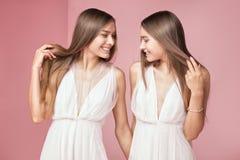 Attraktiva två härliga flickor på rosa bakgrund Arkivfoton