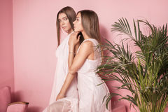 Attraktiva två härliga flickor på rosa bakgrund Royaltyfri Fotografi