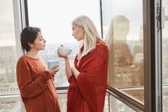 Attraktiva två och sinnliga flickvänner som står nära öppnat fönster i röd kläder, medan dricka kaffe Royaltyfri Foto