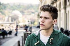 Attraktiva ung mans headshot i stads- inställning arkivfoton