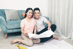 Attraktiva unga asiatiska vuxna par som ser husplan Royaltyfri Bild