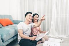Attraktiva unga asiatiska vuxna par som ser husplan Royaltyfria Foton