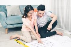 Attraktiva unga asiatiska vuxna par som ser husplan Royaltyfri Fotografi
