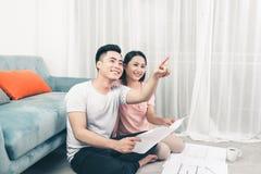 Attraktiva unga asiatiska vuxna par som ser husplan Fotografering för Bildbyråer