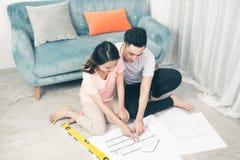 Attraktiva unga asiatiska vuxna par som ser husplan Royaltyfri Foto