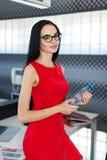Attraktiva unga businesslady i röd klänning och exponeringsglas sitter på tabellen i kontors- och hållvattenflaskan Royaltyfri Fotografi