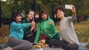 Attraktiva unga damer som yoginien tar selfie som använder smartphonen under picknick parkerar in, i höst Flickor poserar och stock video