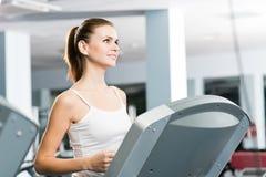 Attraktiva unga kvinnakörningar på en treadmill Royaltyfria Bilder