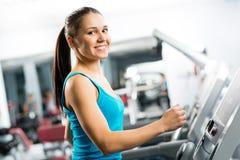 Attraktiva unga kvinnakörningar på en treadmill Royaltyfri Bild