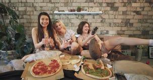 Attraktiva unga kvinnor framme av kameran som spelar som koncentreras mycket i en PSP som tycker om tiden samman med pizza arkivfilmer