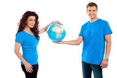 Attraktiva unga par som tillsammans rymmer ett jordklot Royaltyfri Foto