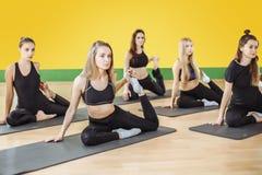Attraktiva unga sportflickor gör yoga tillsammans grupputbildning sund livsstil för begrepp arkivfoto
